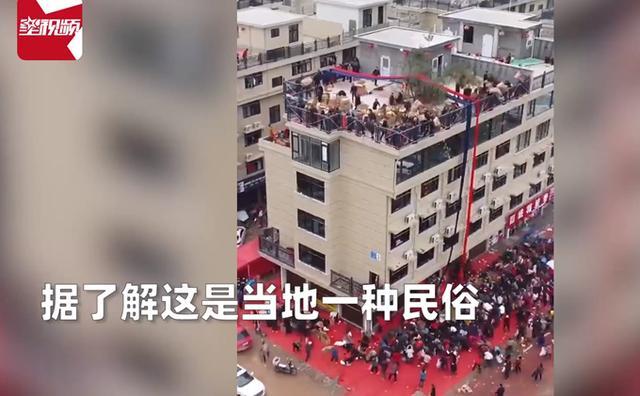房主庆祝乔迁顶楼倾倒几十箱礼物,近百人围观沾喜气,场面壮观